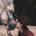 ragazza e cavallo muso contro muso che si guardano.